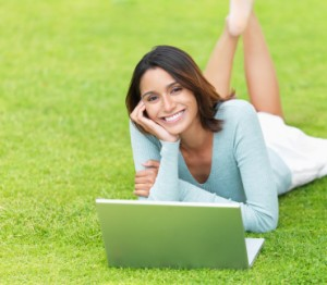 Smiling hispanic girl with laptop lying on grass